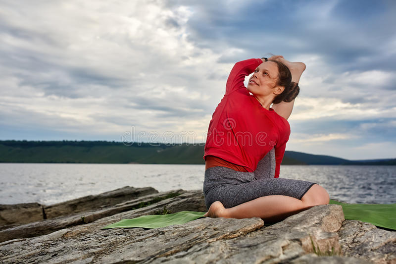 Happy young woman doing yoga exercise outdoors on the stone near river. royalty free stock image