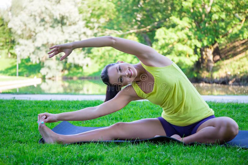 Happy young woman doing yoga exercises in park stock photo