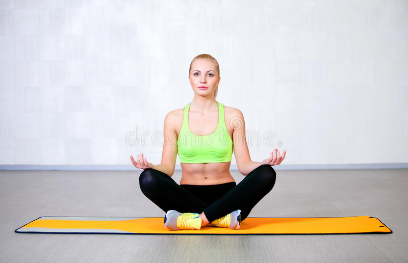 Happy young woman doing yoga exercises sitting in lotus position stock photos