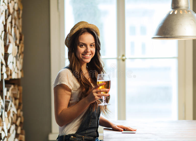 Happy young woman drinking beer at bar or pub royalty free stock images