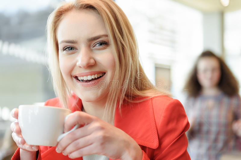 Happy young woman drinking coffee in cafeteria stock images