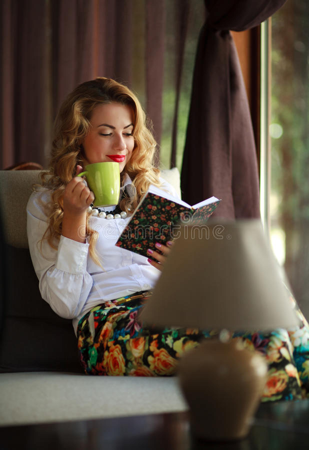 Happy young woman drinking coffee and reading book on couch stock image