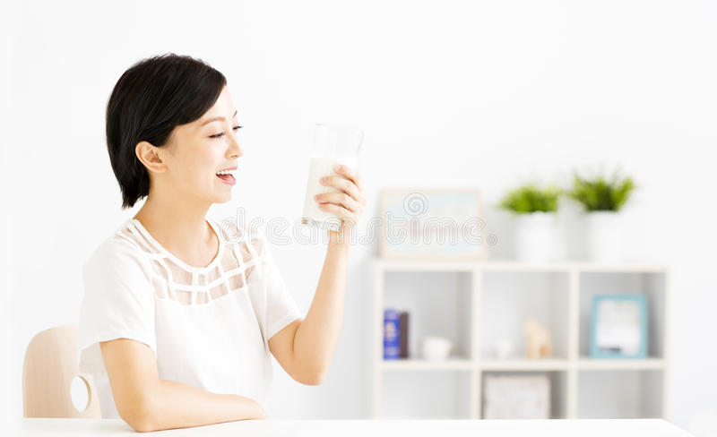 Happy young woman drinking milk stock photos