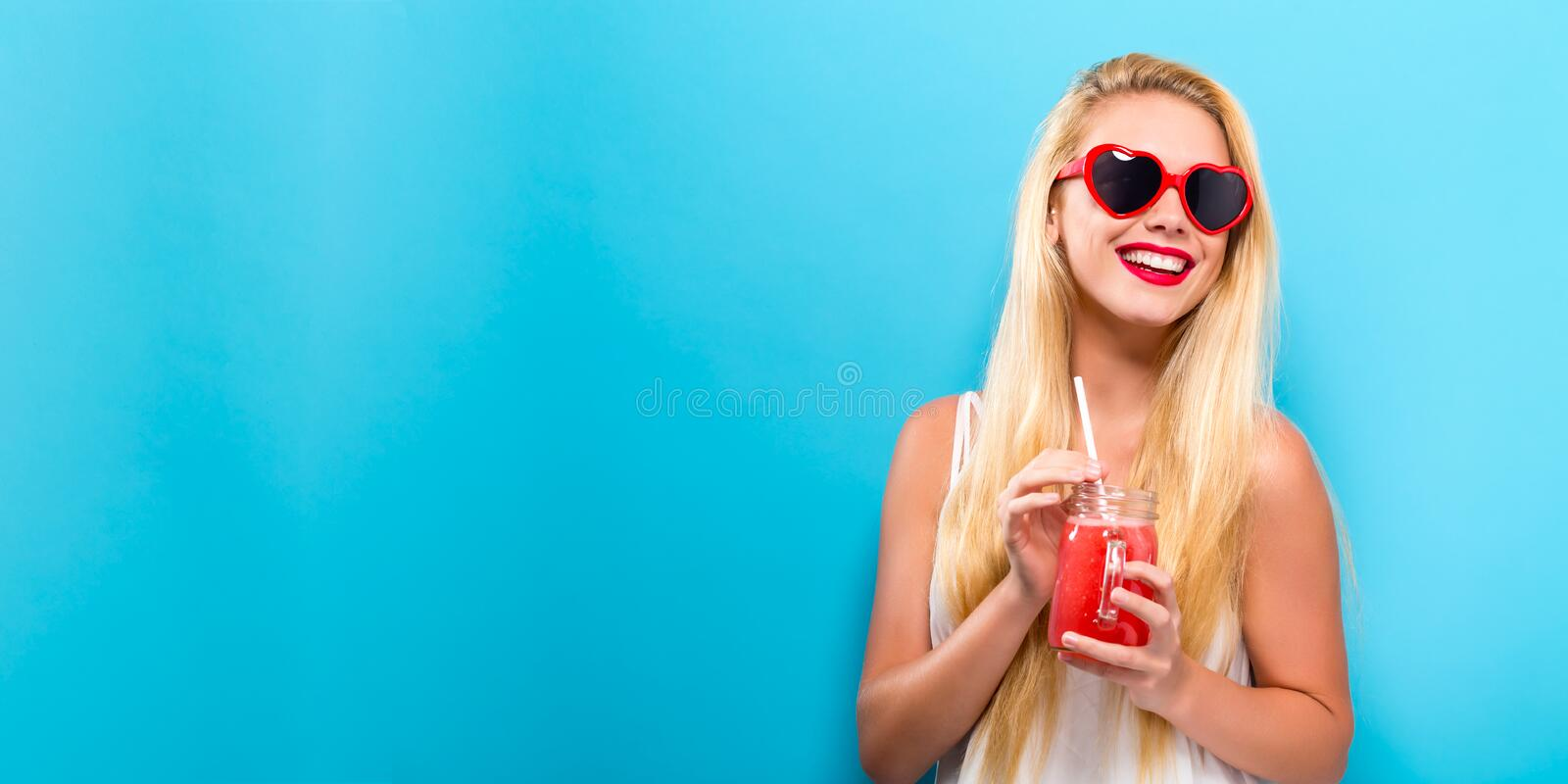 Happy young woman drinking smoothie stock image