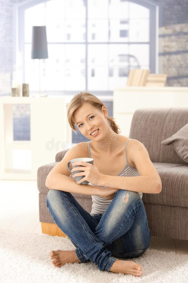 Happy young woman drinking tea at home royalty free stock images