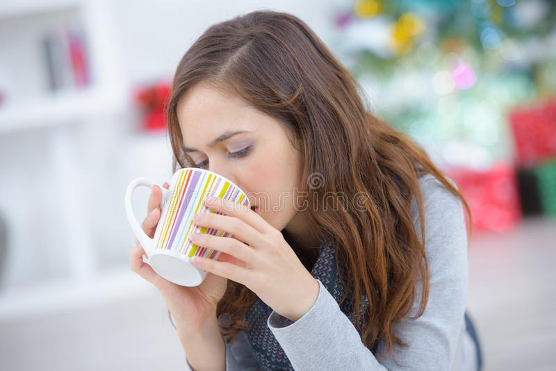 Happy young woman drinking tea at home while relaxing stock photos