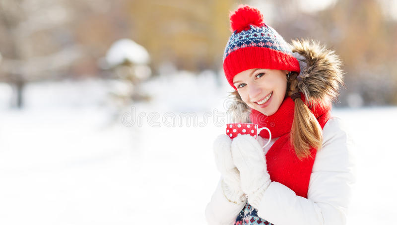 Happy young woman drinking tea in winter stock photography