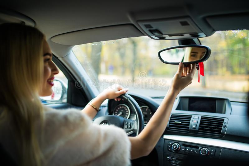 Happy young woman driver looking adjusting rear view car mirror, making sure line is free visibility is good before making turn. S stock photography