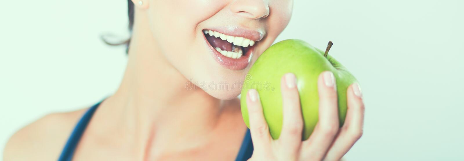 Happy young woman eating apples, isolated on white background stock images