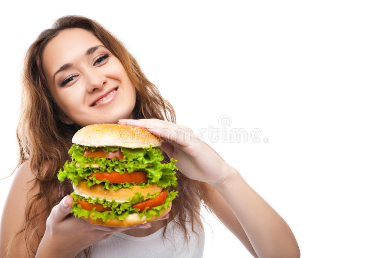 Happy Young Woman Eating big yummy Burger isolated. On white background stock photography