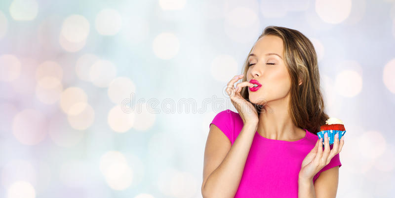 Happy young woman eating birthday cupcake. People, holidays, party, junk food and celebration concept - happy young woman in pink dress eating birthday cupcake stock photo