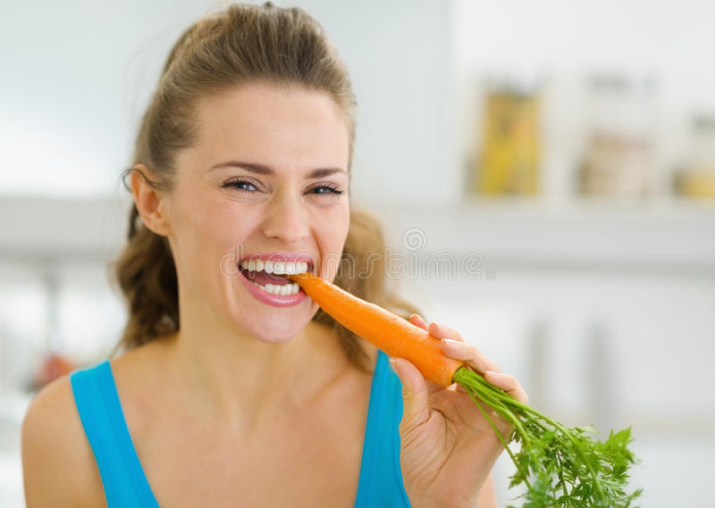 Happy young woman eating carrot in kitchen royalty free stock photos