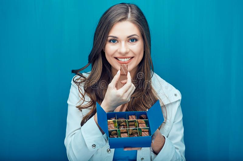 Happy young woman eating chocolate candies. stock photo
