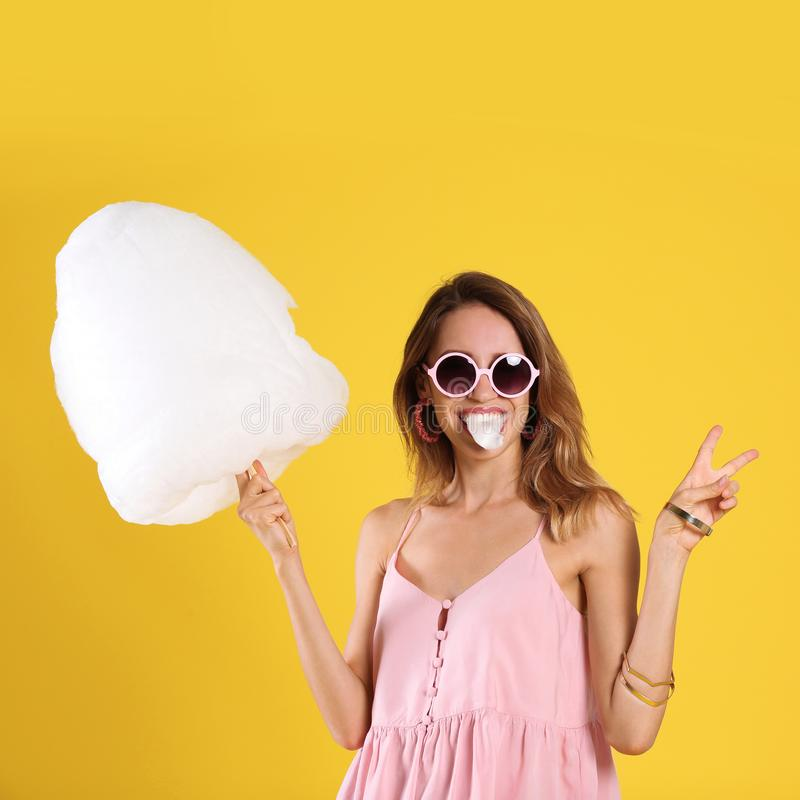 Happy young woman eating cotton candy royalty free stock image