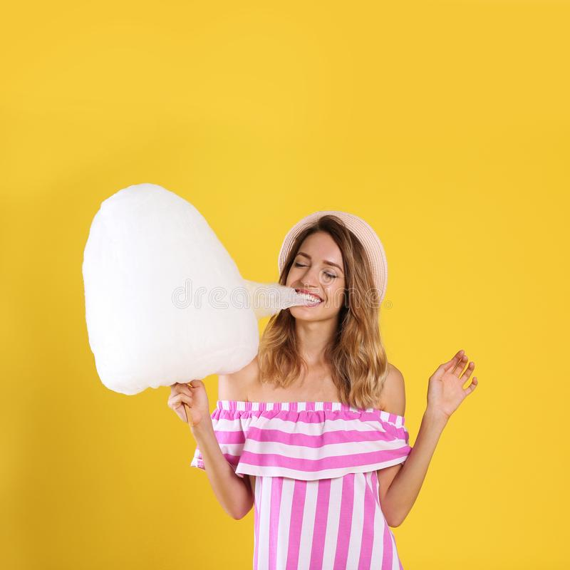 Happy young woman eating cotton candy stock images