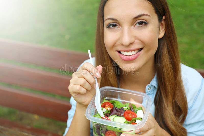 Happy young woman eating healthy salad in the park. Copy space stock photos