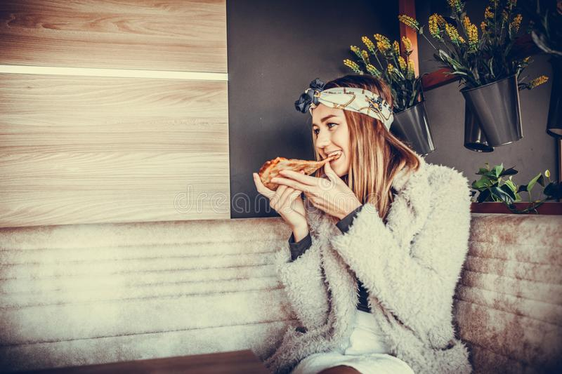 Happy young woman eating pizza in the restaurant stock photography