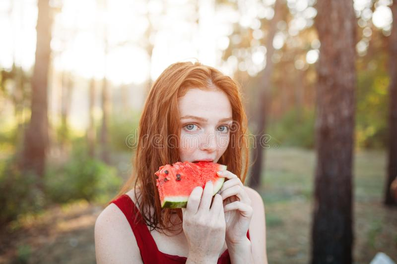 Happy young woman eating watermelon on the nature. Youth lifestyle. Happiness, joy, holiday, beach, summer concept royalty free stock photography