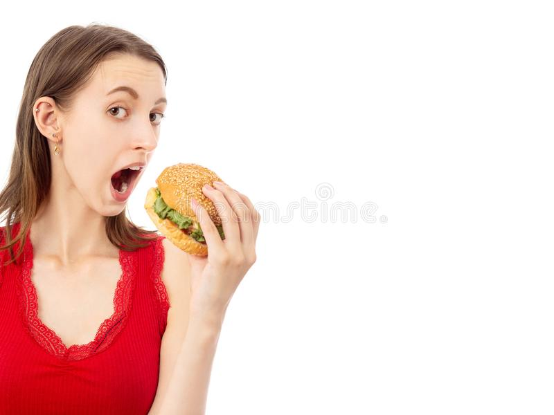 Girl with hamburger. Happy young woman eats hamburger on white background with copy space isolated looking at camera open mouth royalty free stock images