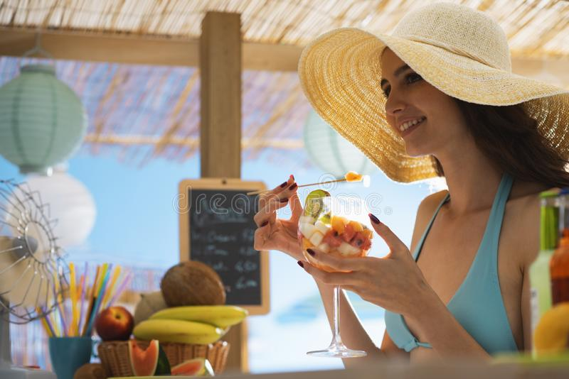 Happy woman at the beach eating a fruit salad royalty free stock images