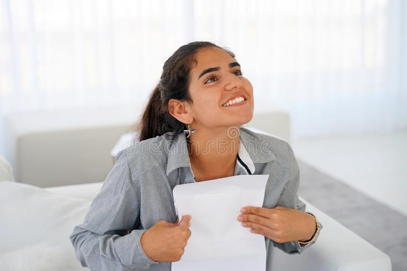 Happy entrepreneur woman reading good news in a letter on sofa stock photography
