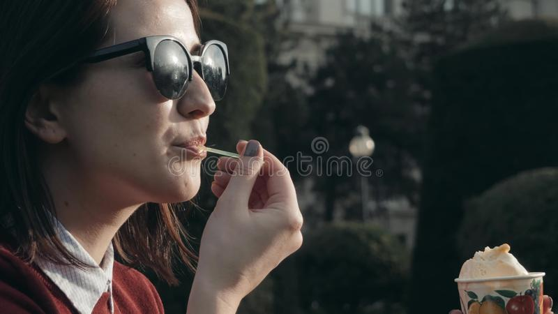 Happy Young Woman Enjoying an Ice Cream Sitting On The Grass At The Park In a Sunny Day stock image