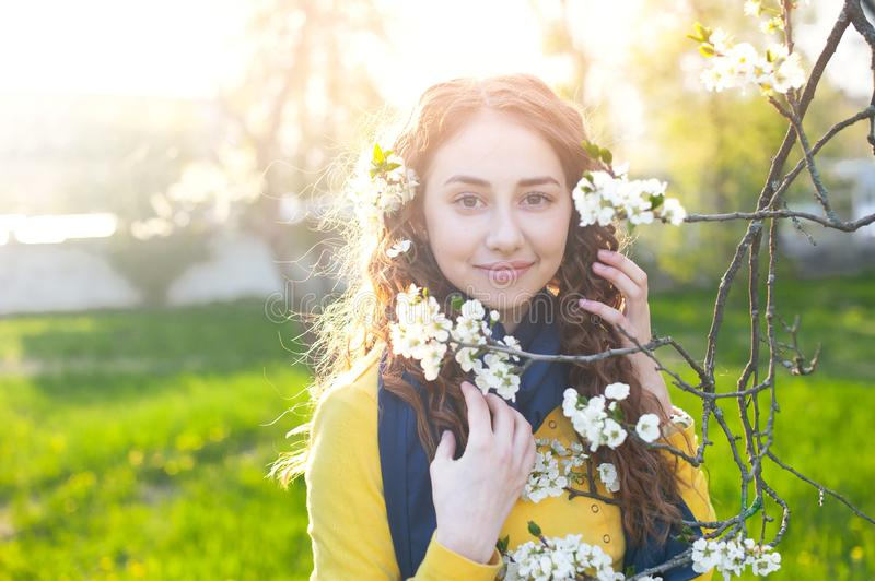 Happy young woman enjoying smell flowers over spring garden background.  stock image
