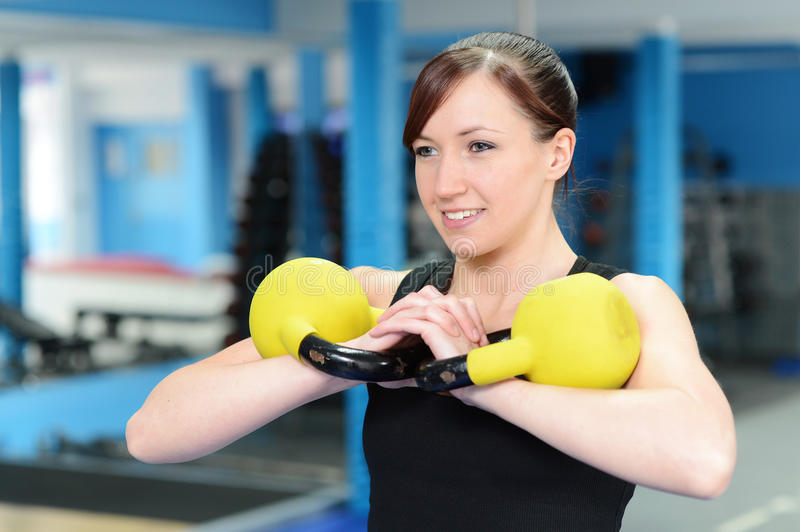 Happy young woman exercising with kettle bell weight. Young woman working out with kettle bell weights, with personal trainer in gym royalty free stock images