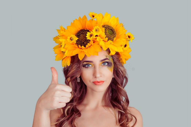 Woman with floral headband showing thumbs up like hand sign royalty free stock images