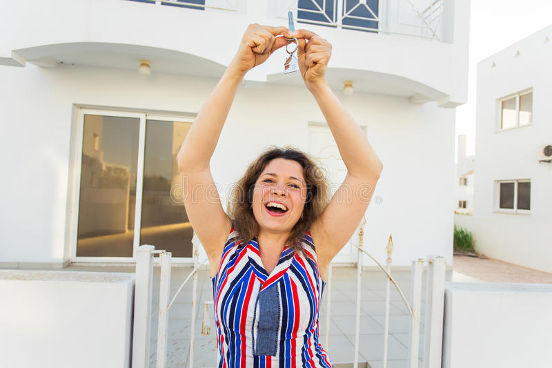 Happy young woman In Front of New Home with New House Keys. Young woman In Front of New Home with New House Keys stock image