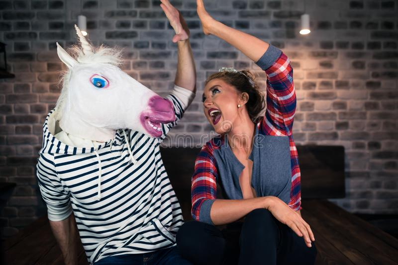 Happy young woman with funny man in comical mask sits on the bed royalty free stock images