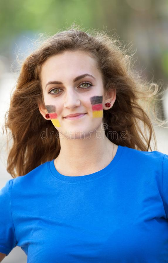 Happy young woman with German flag on cheeks. Cheerful multiracial woman in Germany travel concept. stock photos
