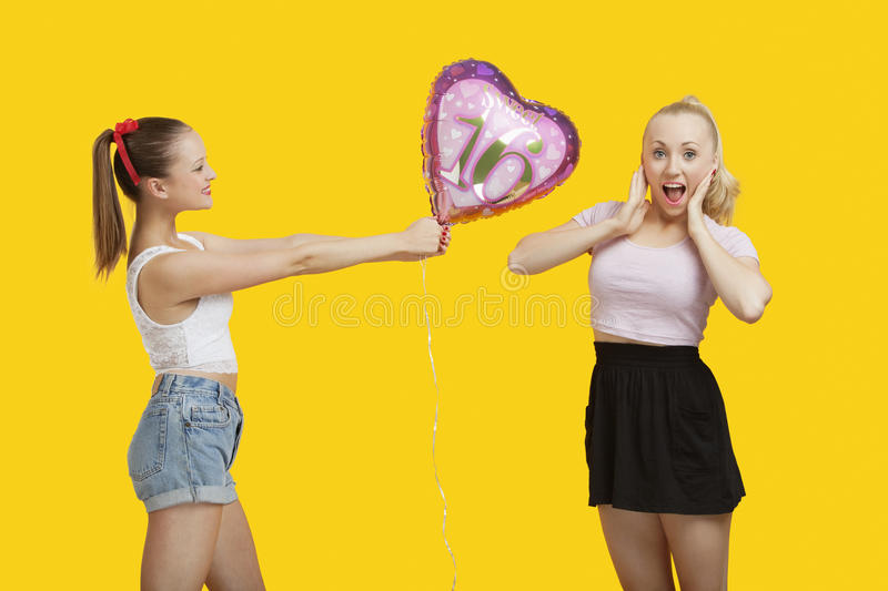 Download Happy Young Woman Giving Birthday Balloon To Amazed Woman Standing Over Yellow Background Stock Photo - Image: 30854878