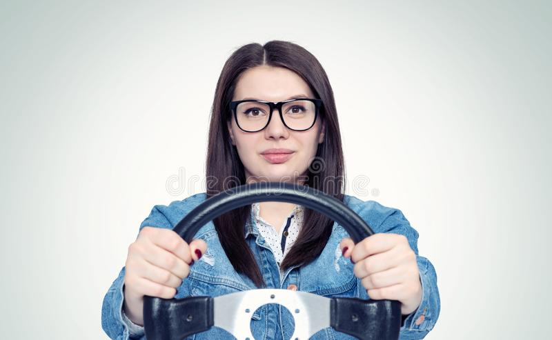 Happy young woman with glasses and car steering wheel, front view, auto concept.  stock photography