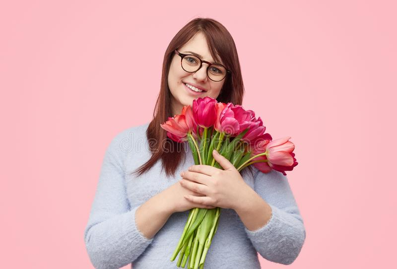 Pretty plump girl with tulips stock photo