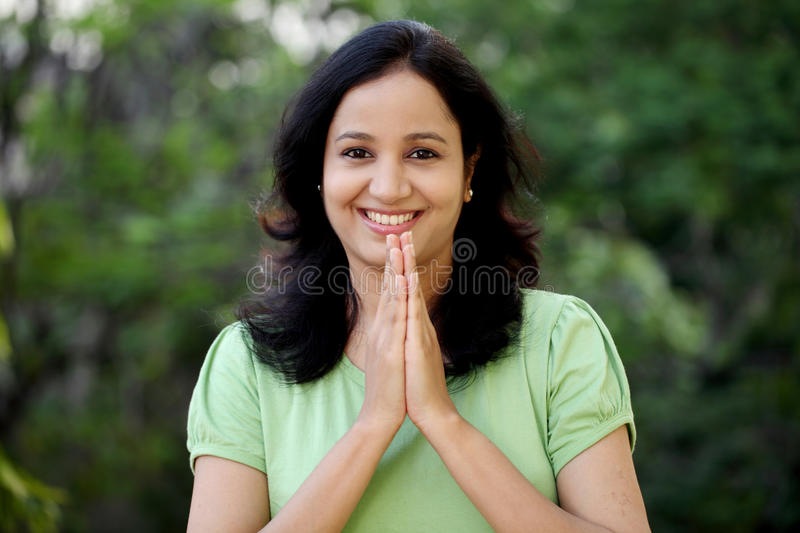 Happy young woman greeting with Namasthe royalty free stock photo