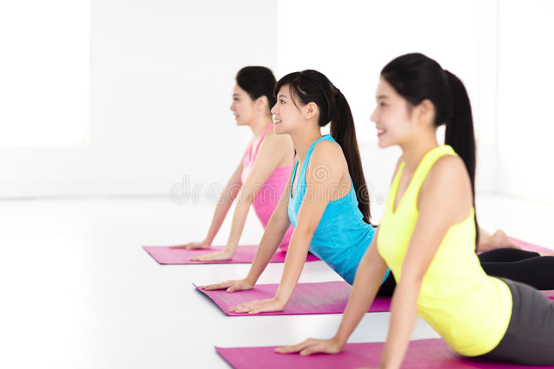 Happy young woman Group doing yoga exercises royalty free stock images