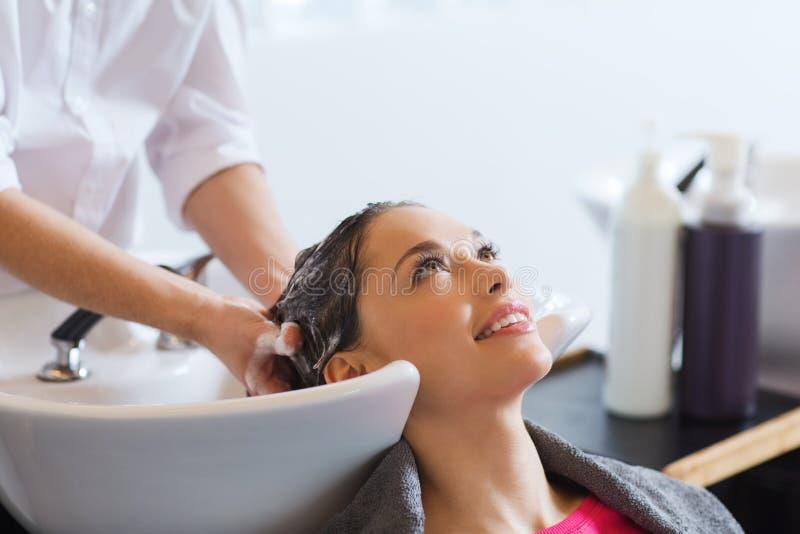 Happy young woman at hair salon royalty free stock image