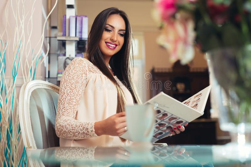 Happy young woman with hairdresser choosing hair color from palette samples at salon royalty free stock photography