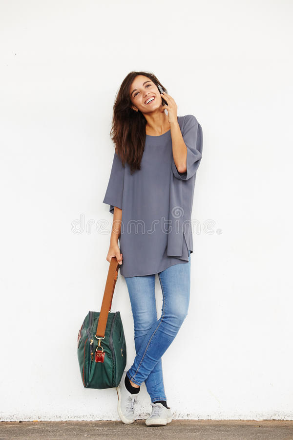 Happy young woman with handbag answering phone call. Full body portrait of happy young woman with handbag answering phone call stock photo