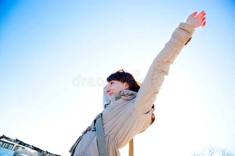 Happy young woman with hands up, sunny day. stock photography