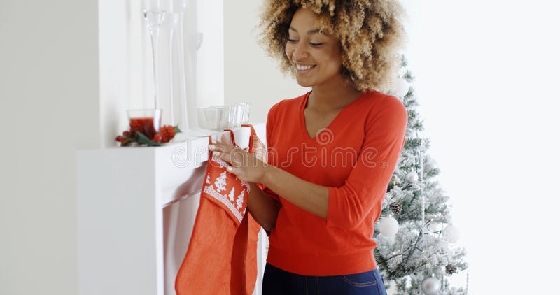 Happy young woman hanging Christmas stockings. Happy young African American woman hanging colorful red Christmas stockings on the mantelpiece of her fireplace to stock photography