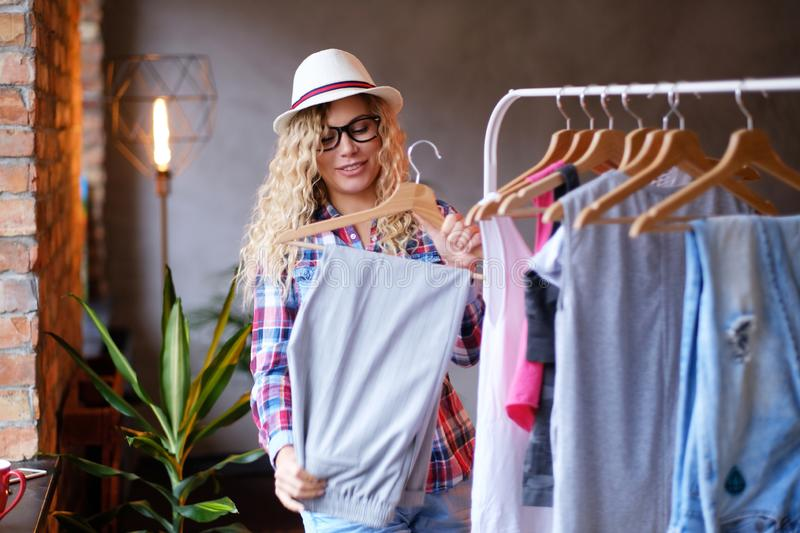 Happy young woman in hat and glasses  is tidy up in her wardrobe for summer at modern loft. royalty free stock image