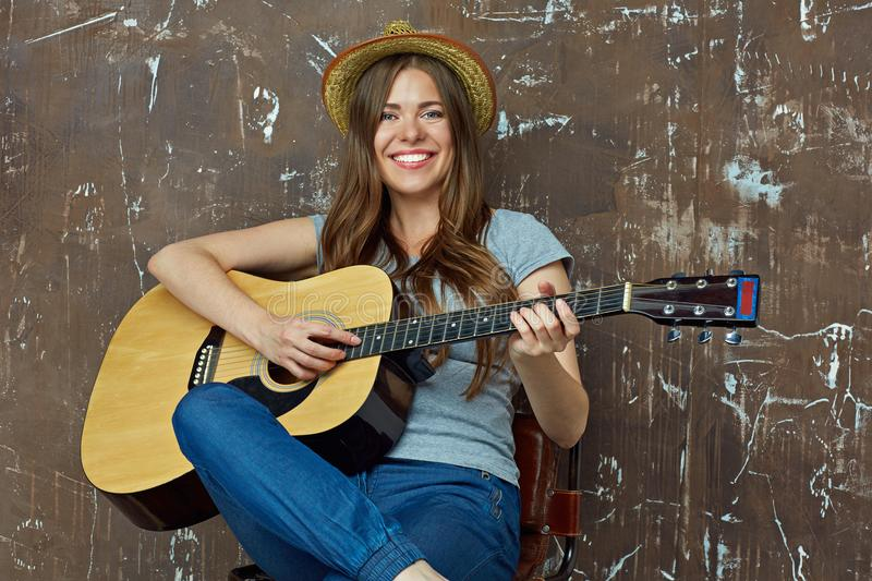 Happy young woman with hat sitting with acoustic guitar on grunge wall. stock images