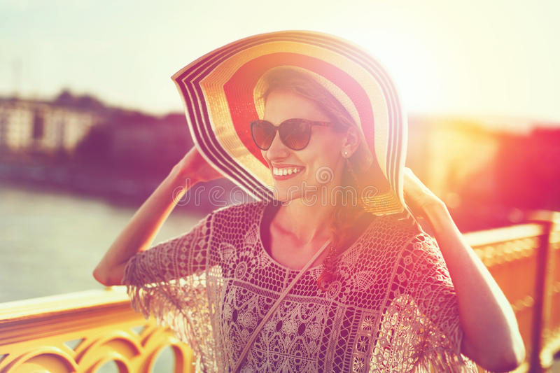 Happy young woman in hat walking on bridge positivity stock photos