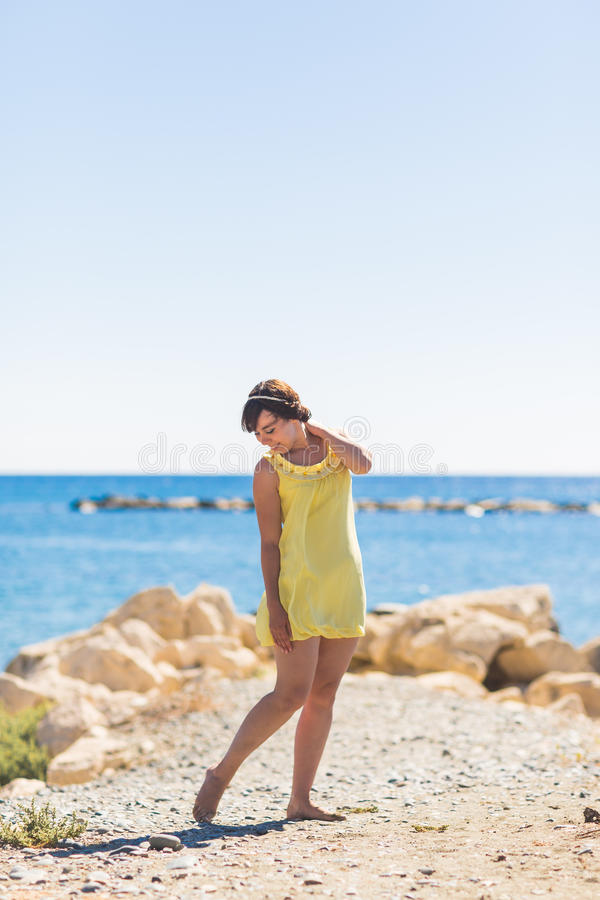 Happy young woman posing on the beach of sea royalty free stock photography
