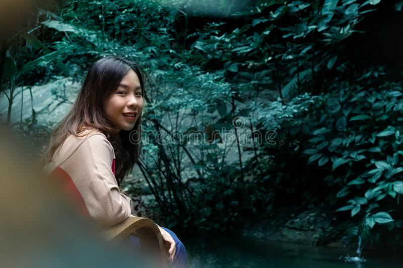 Happy young woman have a rest in garden near a pond. royalty free stock photos