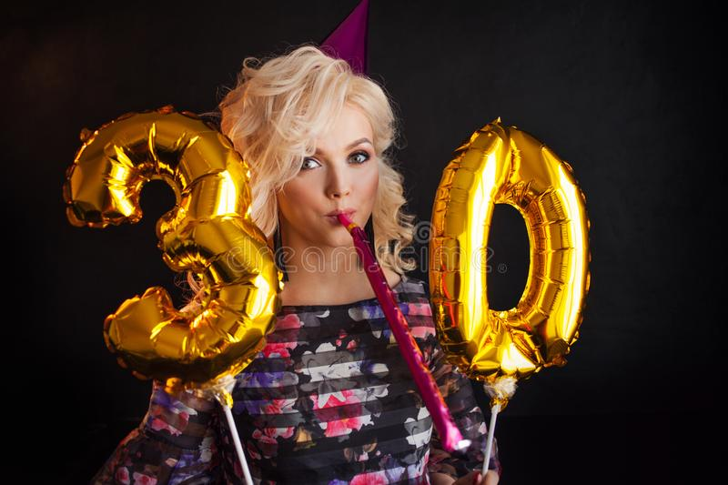 Happy young woman having fun at birthday party. Charming and attractive blonde stock photo