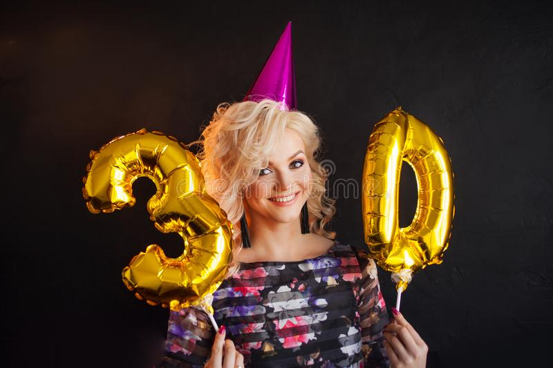 Happy young woman having fun at birthday party. Charming and attractive blonde stock photography