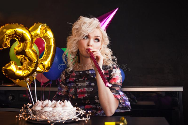 Happy young woman having fun at birthday party. Charming and attractive and festive cake. stock image